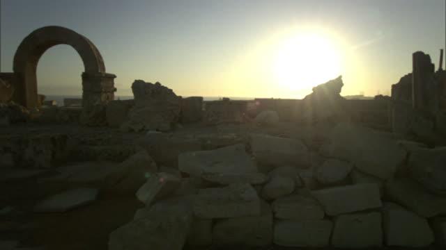 Medium Long Shot crane pan-right - A brilliant sun rises above the Roman ruins of Leptis Magna in Libya. / Leptis Magna, Libya