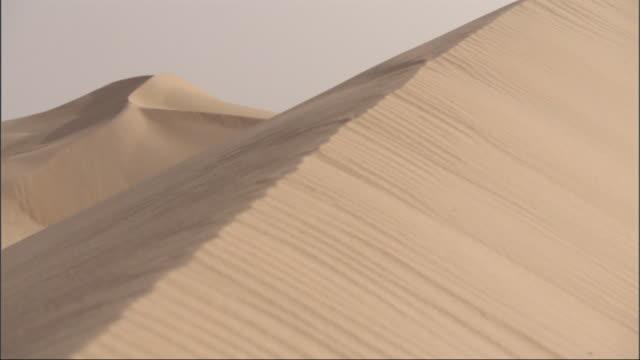 medium long shot, crane tracking-left - sand dunes form unique shapes in the sahara desert in egypt - ägypten stock-videos und b-roll-filmmaterial