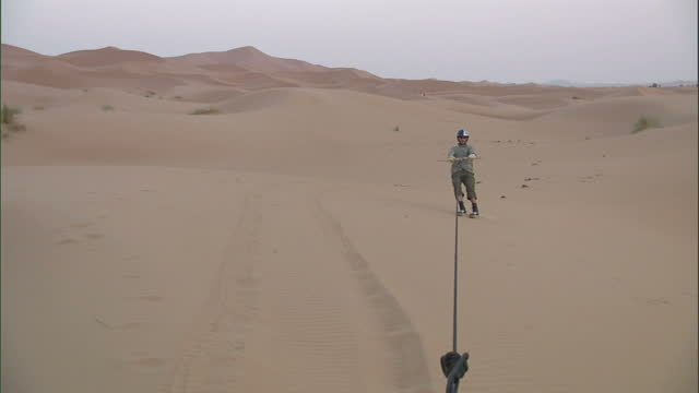 medium long shot hand-held - a young man sand boards across dunes / sahara, egypt - rope stock videos & royalty-free footage