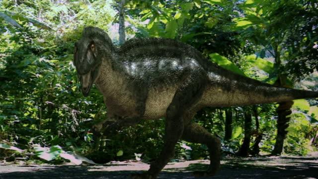 vídeos de stock, filmes e b-roll de medium long shot hand-held pan-left zoom-out - a dinosaur prowls near tropical plants in a computer-generated animation. / washington, d.c., usa - jurássico
