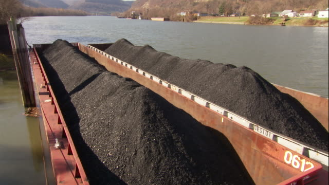 stockvideo's en b-roll-footage met medium long shot hand,held pan,right , coal,filled barges are moored to a riverside dock at a coal distribution facility. / west virginia - hoop samenstelling