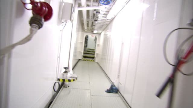 medium long shot hand-held push-in - a long, white corridor leads to a boiler room. / san diego, california, usa - fire extinguisher stock videos & royalty-free footage