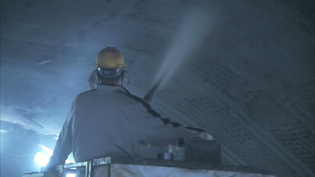 Medium Long Shot hand-held zoom-out - Construction workers spray the domed ceiling of the Niagara Tunnel / Ontario, Canada