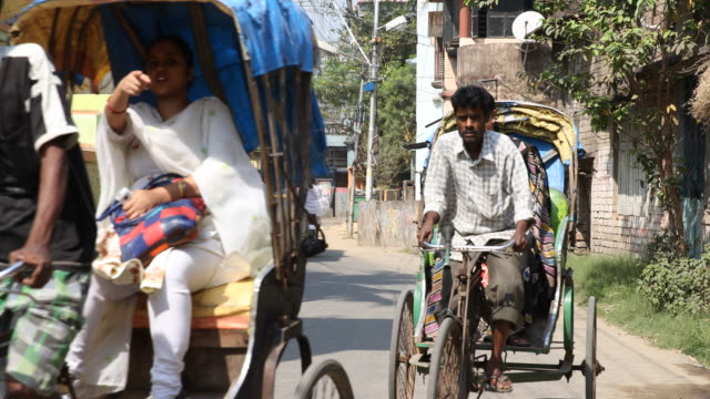 vidéos et rushes de medium long shot on two bicycle rickshaws with passengers driving along a street in kolkata coming towards the camera passing by - pousse pousse