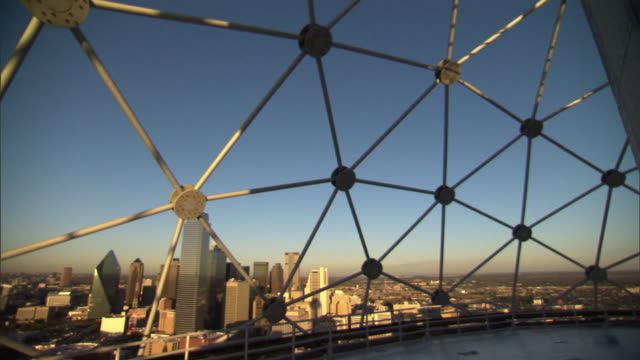 Medium Long Shot pan-left - A geometric structure frames a view of the city of Dallas. / Dallas, Texas, USA