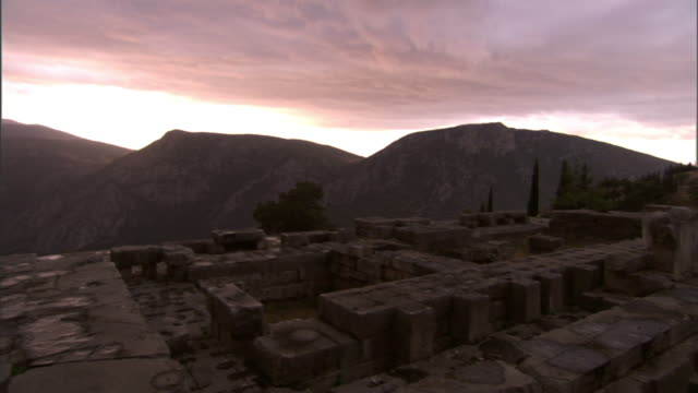 medium long shot pan-left - mountains surround the delphi archeological site in greece. / delphi, greece - greece stock videos & royalty-free footage