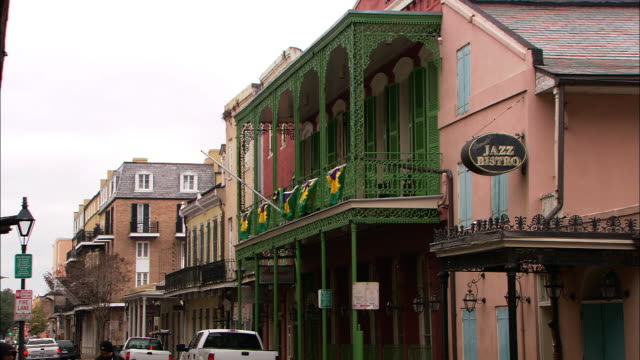 Medium Long Shot pan-left - Signs and awnings decorate a historic New Orleans street. / New Orleans, Louisiana, USA