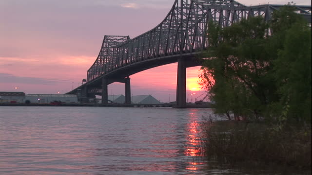 medium long shot pan-left zoom-out - the sun sets behind a bridge in baton rouge, louisiana. / baton rouge, louisiana, usa - baton rouge stock-videos und b-roll-filmmaterial