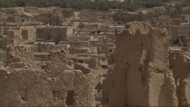 Medium Long Shot, pan-right - An aerial view shows a vast deserted city with crumbling adobe buildings / Egypt