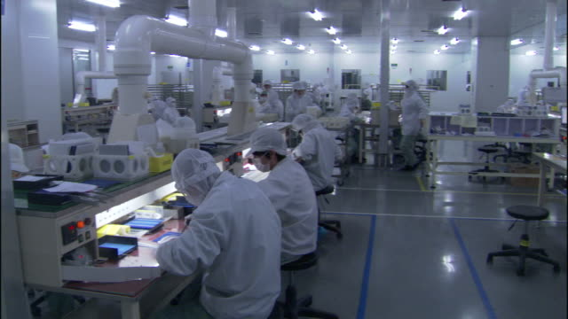 Medium Long Shot pan,right , Lab technicians wear protective clothing. / California