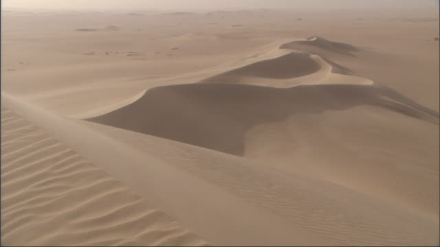Medium Long Shot, pan-right - Shadows fall across a vast landscape of golden sand dunes / Egypt