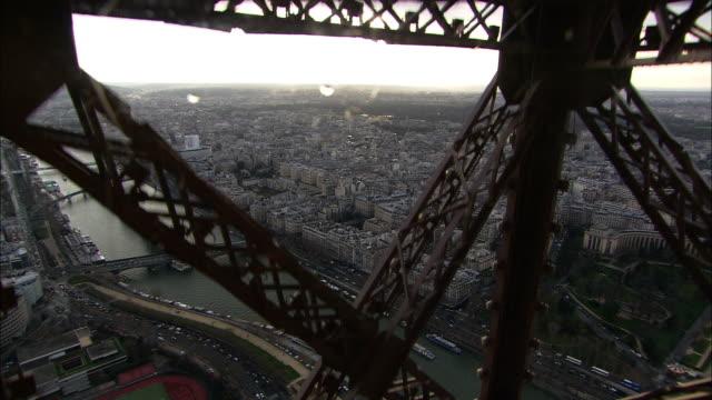 vidéos et rushes de medium long shot pan-right - the crossbeams of the eiffel tower frame a view of the city of paris far below. / paris, france - poutrelle