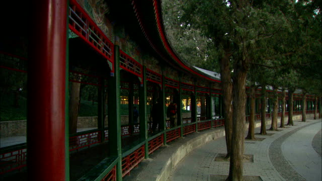 medium long shot pan-right - two pedestrians walk along the curved walkway of the summer palace./beijing, china - summer palace beijing stock videos & royalty-free footage
