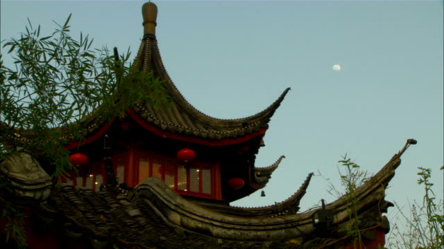 medium long shot pan-right zoom-in - a gibbous moon glows above a pagoda./nanjing, china - temple building stock videos & royalty-free footage