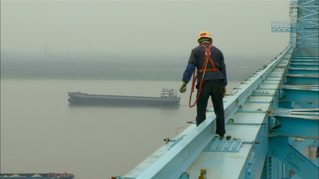 medium long shot pan-right zoom-out - a construction worker stands on the yangtze river bridge./nanjing, china - nanjing stock videos & royalty-free footage