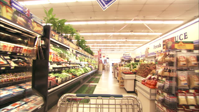 stockvideo's en b-roll-footage met medium long shot push-in - a shopping cart moves through the produce department in a grocery store - supermarkt