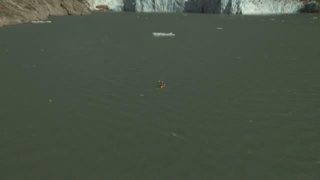 'Medium Long Shot push-in tilt-down-Adventurers paddle their kayak near the snout of a glacier. / Alaska, USA'