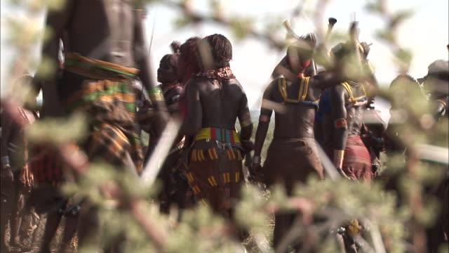stockvideo's en b-roll-footage met medium long shot rack-focus - natives dance while holding instruments near a thorn bush. / ethiopia - inheemse cultuur