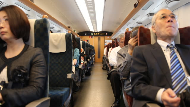 medium long shot showing the train compartment with passengers seated a female voice welcomes the passengers and announces the next station - kyushu shinkansen stock videos and b-roll footage