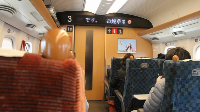 medium long shot showing the train compartment with passengers seated focussing on the led display where can be read ladies and gentlemen welcome to... - kyushu shinkansen stock videos and b-roll footage