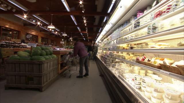 medium long shot static _ an employee stocks the shelves in a supermarket deli as customers shop / watertown, massachusetts, usa - formaggio video stock e b–roll