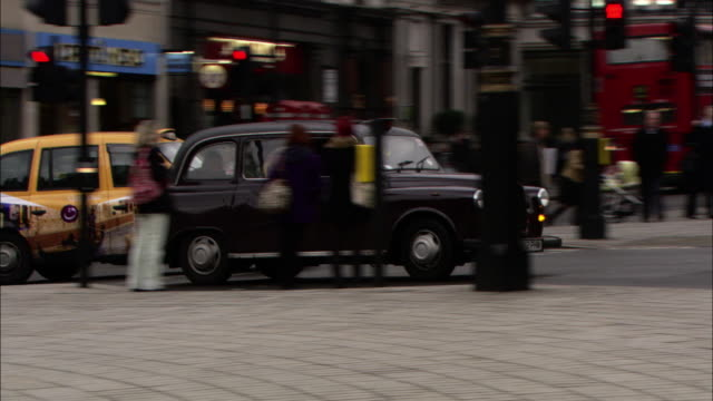medium long shot static - a black taxicab drives through an intersection and down a street. / london, england - taxi stock videos & royalty-free footage