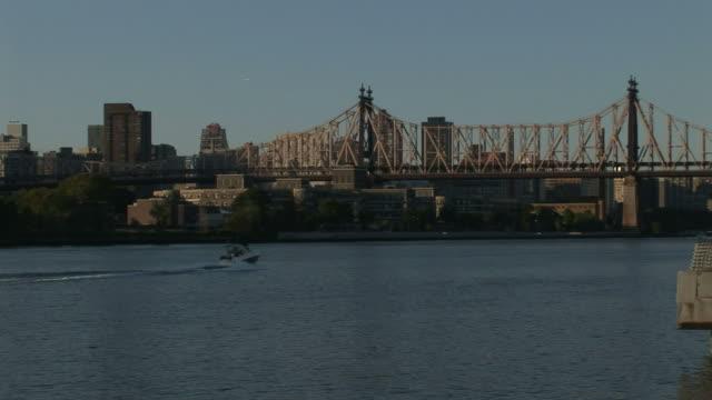 medium long shot  static - a boat cruises along a river between new york city and queens. /  new york city - kantilever bildbanksvideor och videomaterial från bakom kulisserna