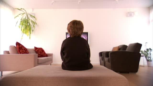 medium long shot static - a boy sits on an ottoman and watches television.   - one person stock videos & royalty-free footage