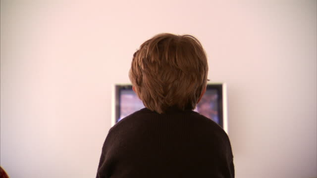Medium Long Shot static - A boy watches television.