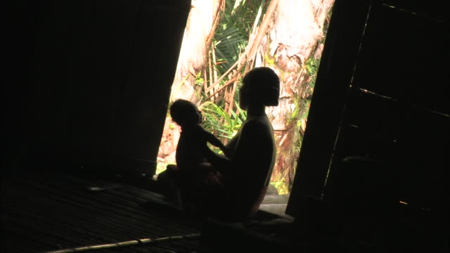 Medium Long Shot static - A mother sits in silhouette with her baby in a dark room. / Indonesia