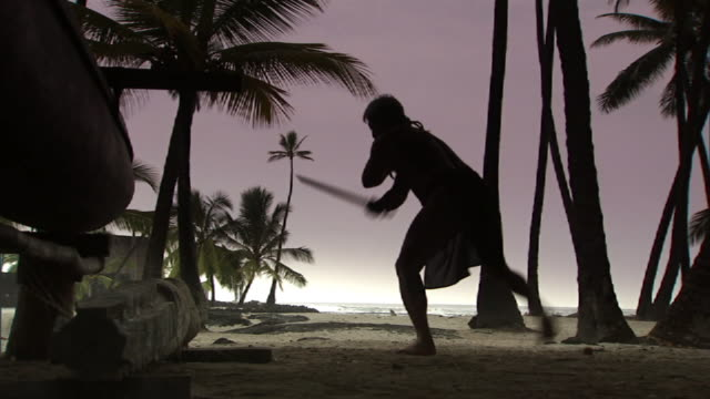 medium long shot static - a silhouetted hula dancer swings a sword on a beach at the place of refuge on hawaii's big island. / hawaii, usa - hawaiianische kultur stock-videos und b-roll-filmmaterial