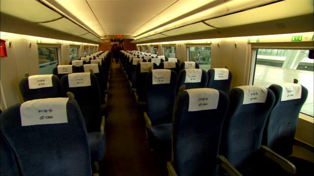 medium long shot static - an employee walks down the aisle of a train, arranging the seats./beijing, china - interno di treno video stock e b–roll