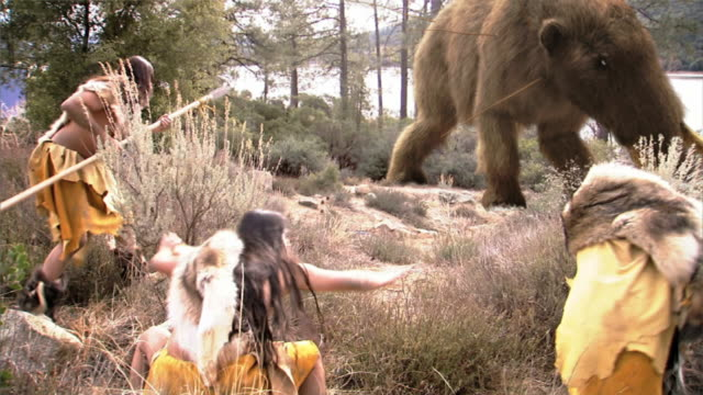 Medium Long Shot static - Clan hunters throw spears at a woolly mammoth. /