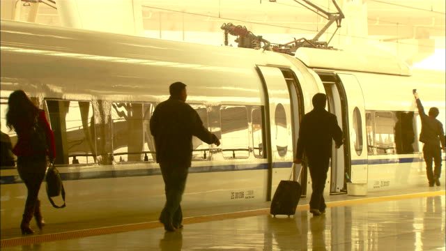 medium long shot static - commuters walk through the bright light in beijing south station./beijing, china - high speed train stock videos & royalty-free footage