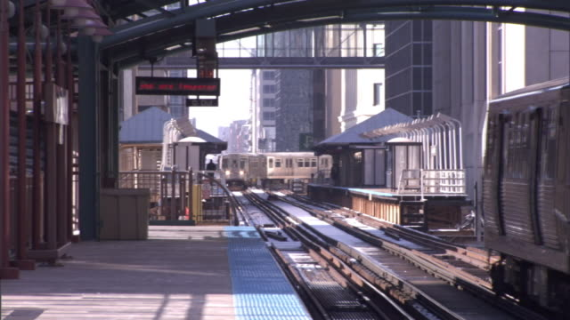 medium long shot static - elevated trains pass one another near a train station. / chicago, illinois, usa - chicago elevated stock-videos und b-roll-filmmaterial