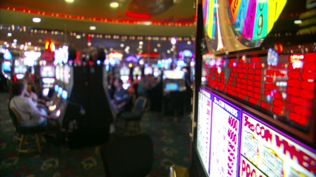 medium long shot static - gamblers play slot machines in a brightly lit las vegas casino. / las vegas, nevada, usa - kasino stock-videos und b-roll-filmmaterial