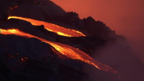 medium long shot static - glowing lava flows from a volcanic eruption on hawaii's big island. / hawaii, usa - lava stock videos & royalty-free footage