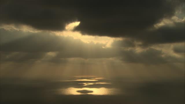 Medium Long Shot static - Golden sunbeams shine through dark clouds and glow above the ocean. / Israel