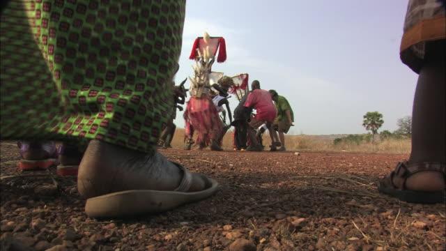 Medium Long Shot static - Natives dance in a circle in Benin. / Benin