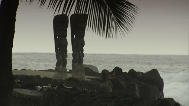 medium long shot static - pacific waves crash onto a beach near tikis on hawaii's big island. / hawaii, usa - hawaiian culture stock videos & royalty-free footage