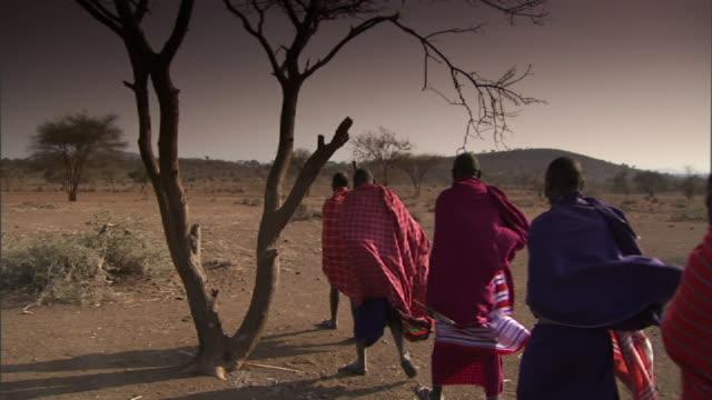 medium long shot static - robed members of a masai tribe walk across a dry, windy plain in tanzania. / tanzania - stamm stock-videos und b-roll-filmmaterial