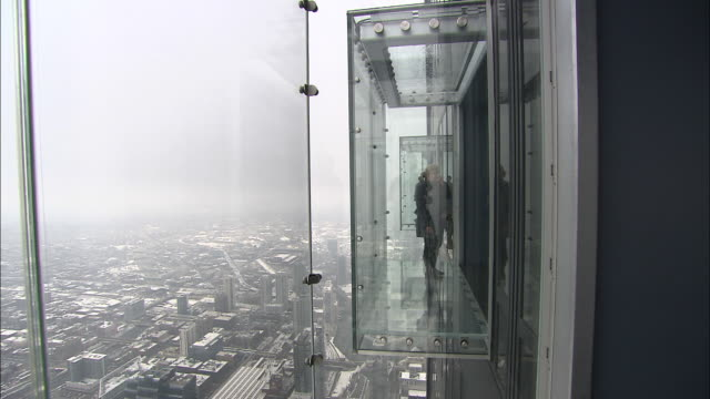medium long shot static - several women step out onto the glass viewing platforms high on the outside of chicago's sears tower. / chicago, illinois, usa - willis tower stock videos and b-roll footage