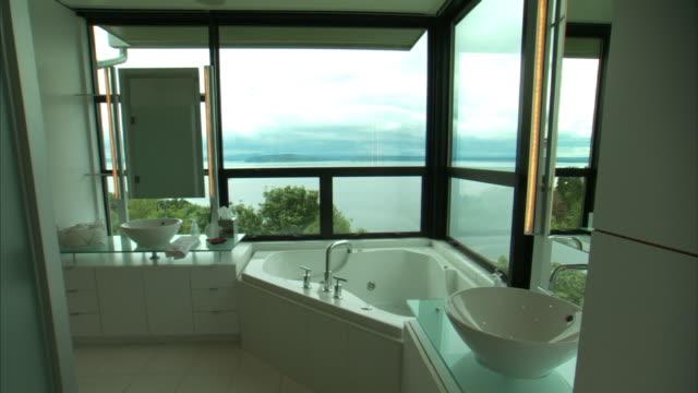 Medium Long Shot static - Sunlight shines through large windows in a modern bathroom. / Seattle, WA