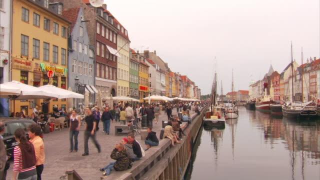 vídeos y material grabado en eventos de stock de medium long shot static - tourists walk near a scenic canal. / copenhagen, denmark - oresund escandinavia
