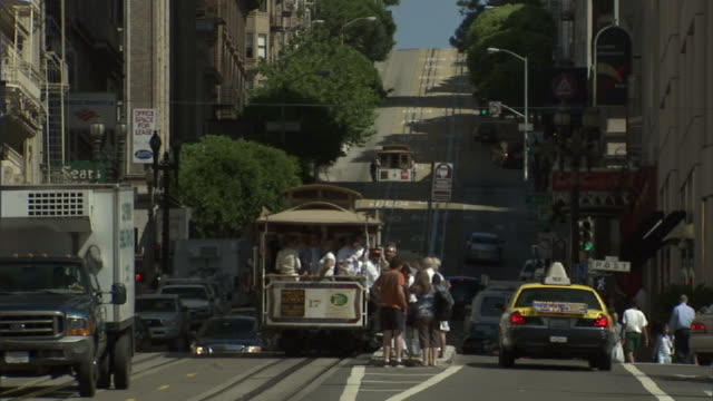 medium long shot static - traffic passes a trolley and pedestrians in san francisco. / san francisco, california, usa - trolley bus stock videos & royalty-free footage