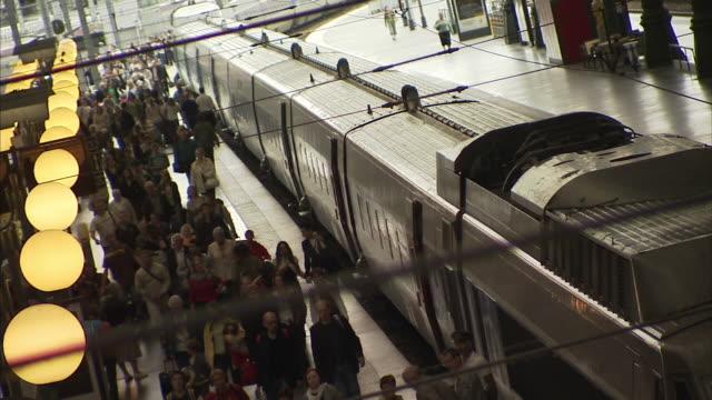 Medium Long Shot static - Travelers walk alongside a train in a station. / Paris, France