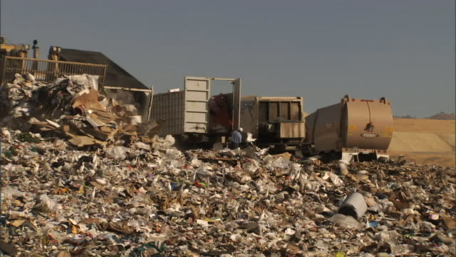 medium long shot static - trucks dump garbage as bulldozers spread it at a landfill / bakersfield, california - rubbish dump stock videos & royalty-free footage