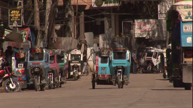 Medium Long Shot static - Tuk-tuks pass pedestrians and other traffic on a busy street in Bontuc, Philippines. / Bontuc, Philippines