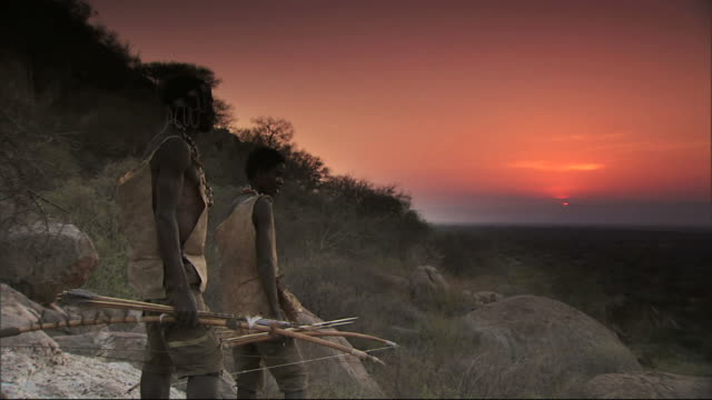 medium long shot static - two hadza hunters stand on a ridge and watch the sun set. / hadza, united republic of tanzania - archery bow stock videos and b-roll footage