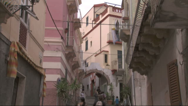 medium long shot tilt-down - two tourists hold hands as they climb the steps in an alleyway in sardinia, italy. / sardinia, italy - sardinien stock-videos und b-roll-filmmaterial